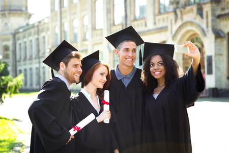 Young students dressed in black graduation gown. Campus as a background. Boys and girls smiling, hugging, holding diplomas and making photo on mobile phone