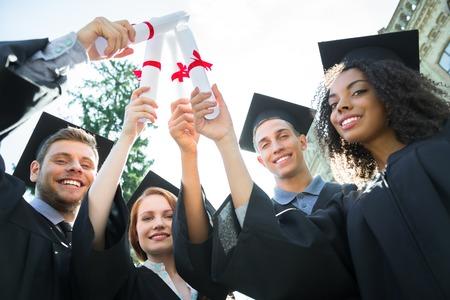 Jonge studenten gekleed in zwarte afstuderen jurk. Campus als achtergrond. Jongens en meisjes die vrolijk glimlachen, diploma's houden als zwaarden en camera bekijken. Onderaanzicht foto Stockfoto