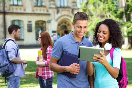 successful student: Photo of young group of students with backpacks and books. Campus as a background. Girl and boy using tablet computer. Students are on background