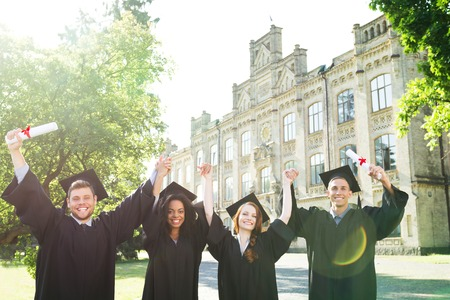 Young students dressed in black graduation gown. Campus as a background. Boys and girls cheerfully smiling, looking at camera and holding hands up. Light flare on photo Stock Photo