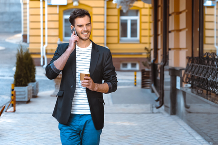 Portrait of stylish handsome young man with bristle standing outdoors. Man wearing jacket and shirt. Smiling man talking on mobile phone and holding cup of coffee