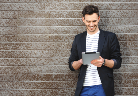 young adult men: Portrait of stylish handsome young man with bristle standing outdoors. Man wearing jacket and shirt. Smiling man using tablet computer and leaning against wall Stock Photo