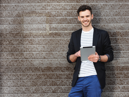 Portrait of stylish handsome young man with bristle standing outdoors. Man wearing jacket and shirt. Smiling man using tablet computer and leaning against wall Фото со стока