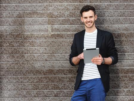 Portret van stijlvolle knappe jonge man met haren die zich in openlucht. Man met jasje en shirt. Lachende man met behulp van tablet-computer en leunend tegen de muur