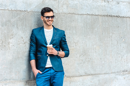 Portret van stijlvolle knappe jonge man met haren die zich in openlucht. Man met jasje en shirt. Lachende man met een zonnebril met een kopje koffie en leunend tegen de muur