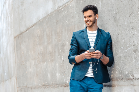 bristle: Portrait of stylish handsome young man with bristle standing outdoors. Man wearing jacket and shirt. Smiling man listening to music on headphones and leaning against wall