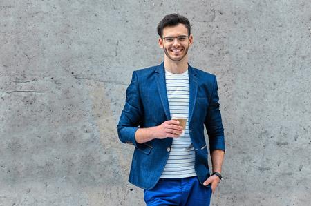 屋外で立って毛とスタイリッシュなハンサムな若い男の肖像画。ジャケットとシャツを着た男。グラス一杯のコーヒーを保持していると、壁にもた