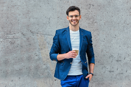 Portrait of stylish handsome young man with bristle standing outdoors. Man wearing jacket and shirt. Smiling man with glasses holding cup of coffee and leaning against wall