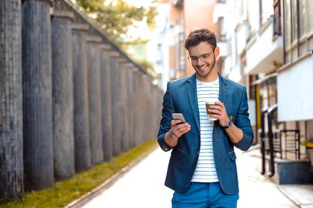 강모 야외 서 세련된 잘 생긴 젊은 남자의 초상화. 재킷과 셔츠를 착용하는 사람 (남자). 안경 커피 잔을 들고와 휴대 전화를 사용 함께 웃는 남자 스톡 콘텐츠