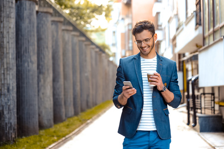 Portrait of stylish handsome young man with bristle standing outdoors. Man wearing jacket and shirt. Smiling man with glasses holding cup of coffee and using mobile phone 免版税图像