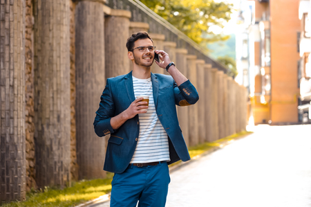 Portrait of stylish handsome young man with bristle standing outdoors. Man wearing jacket and shirt. Smiling man with glasses holding cup of coffee and talking on mobile phone