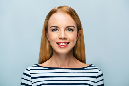woman standing: Portrait of beautiful caucasian blonde woman standing on grey background. Young woman smiling and looking at camera
