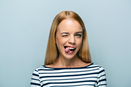 lingua fuori: Portrait of beautiful caucasian blonde woman standing on grey background. Young woman with tongue out  looking at camera Archivio Fotografico