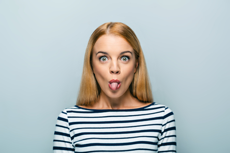 lengua afuera: Portrait of beautiful caucasian blonde woman standing on grey background. Young woman with tongue out  looking at camera Foto de archivo