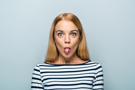 lengua afuera: Retrato de la hermosa mujer rubia cauc�sica de pie sobre fondo gris. Mujer joven con la leng�eta mirando hacia la c�mara Foto de archivo