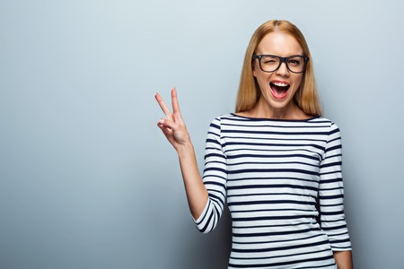 victory sign: Portrait of beautiful caucasian blonde woman standing on grey background. Young woman with glasses cheerfully smiling and showing victory sign Stock Photo