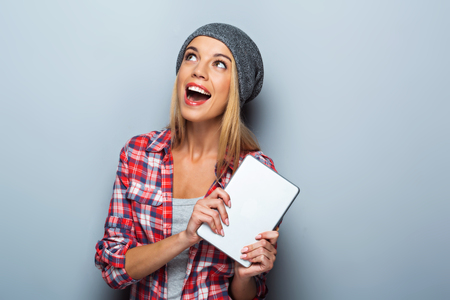 cheerfully: Portrait of beautiful caucasian blonde woman standing on grey background. Young woman with hat cheerfully smiling and holding tablet computer