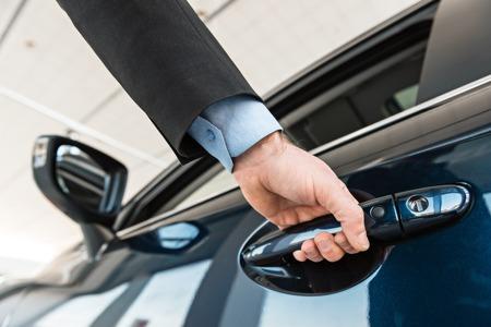 Close-up foto van de jonge man de hand aan te raken en openning nieuwe auto. Concept voor autoverhuur