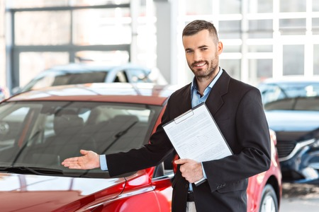Photo of young male consultant showing new car in auto show. Concept for car rental