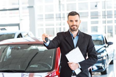 若い男性コンサルタントの新しい車を示し、自動車ショーでそれにキーを押しの写真。レンタカーのコンセプト