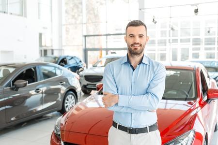 Foto van de jonge man die in de buurt van nieuwe auto in autoshow. Concept voor autoverhuur Stockfoto