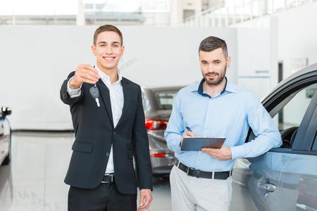 Photo d'un jeune consultant de sexe masculin présentant une nouvelle voiture à un acheteur et tenant des clés dans un salon de l'automobile. Concept pour la location de voiture