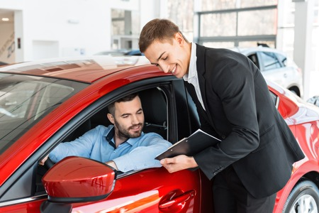 auto sales: Photo of young male consultant and buyer signing contract for new car in auto show. Concept for car rental Stock Photo