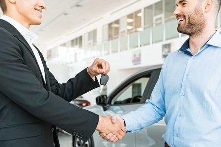 自動車ショーの巧妙な取り引き後に買い手に車のキーを与える若い男性コンサルタントの写真。レンタカーのコンセプト