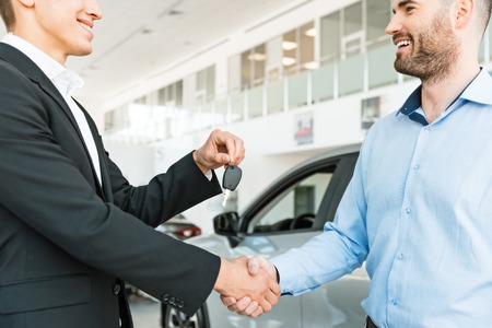 car salesperson: Photo of young male consultant giving car key to buyer after successful deal in auto show. Concept for car rental