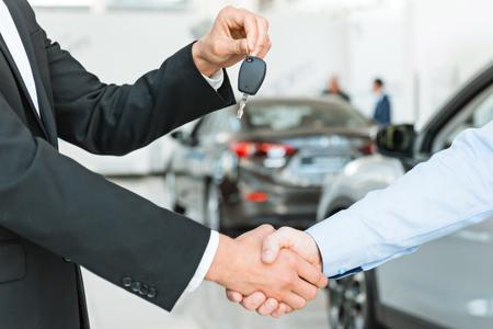 Photo de jeune consultant mâle donnant clé de voiture à l'acheteur après beaucoup de succès dans salon de l'auto. Concept pour la location de voiture
