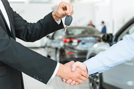 deal in: Photo of young male consultant giving car key to buyer after successful deal in auto show. Concept for car rental