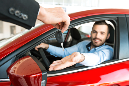 car salesperson: Photo of young man sitting inside new car and getting keys to it. Concept for car rental