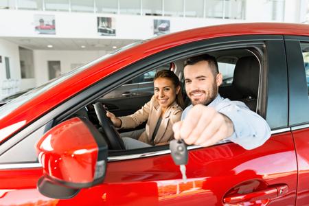 Foto di giovani coppie che si siedono dentro la nuova automobile. Uomo che mostra le chiavi. Concetto di noleggio auto Archivio Fotografico - 47712859
