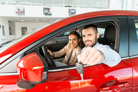 Photo of young couple sitting inside new car. Man showing keys to it. Concept for car rental