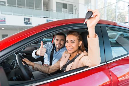 Foto des jungen Paares im Inneren neuen Auto zu sitzen. Frau hält Schlüssel zu ihm. Man lächelt und zeigt Daumen nach oben. Konzept für Autovermietung