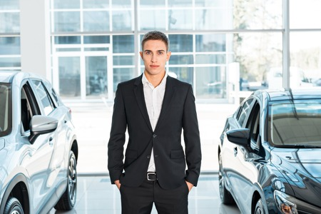 Photo of young male consultant in auto show. Consultant standing near cars and looking at camera. Concept for car rental