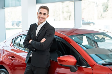 Photo of young male consultant in auto show. Consultant leaning on car and smiling. Concept for car rental