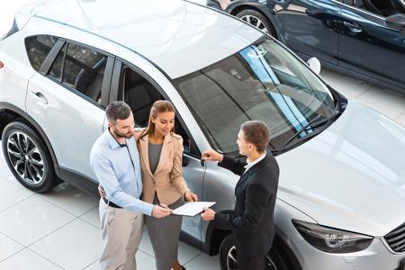 Draufsicht Foto der jungen männlichen Berater und Käufer Vertrag in Auto-Show für neues Auto zu unterzeichnen. Konzept für Autovermietung Standard-Bild