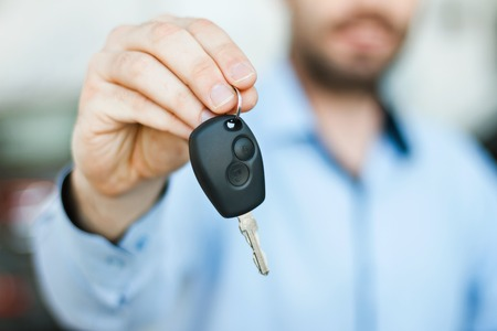 car salesperson: Close up photo of happy young man showing key to his new car. Concept for car rental. Focus on key Stock Photo