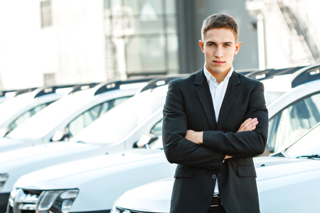 Photo of young male consultant in auto show. Consultant standing near row of cars and looking at camera. Concept for car rental