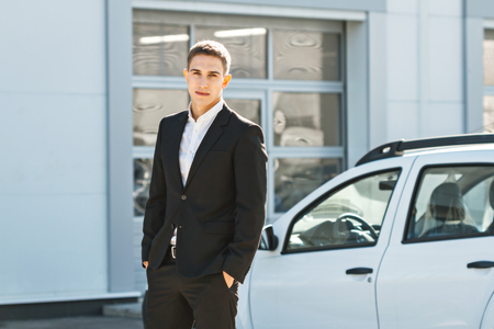 Photo of young male consultant near auto show. Consultant standing near car and looking at camera. Concept for car rental