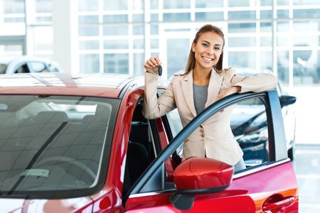 그녀의 새 차에 키를 보여주는 행복 젊은 혼합 된 경주 여자의 사진입니다. 자동차 대여에 대한 개념 스톡 콘텐츠