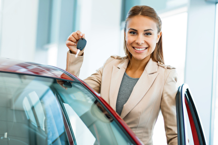 Photo of happy young mixed race woman showing key to her new car. Concept for car rental Stok Fotoğraf