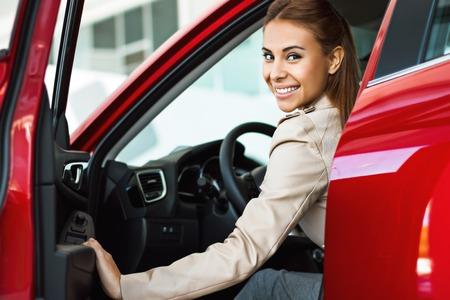 Foto der glücklichen jungen gemischten Rennen Frau in ihrem neuen Auto zu sitzen. Konzept für Autovermietung