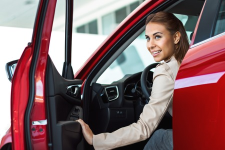 car salesperson: Photo of young smiling mixed race woman sitting inside her new car. Concept for car rental
