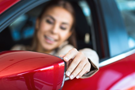 sale: Photo of happy young mixed race woman sitting inside her new car and looking at sideview mirror. Concept for car rental