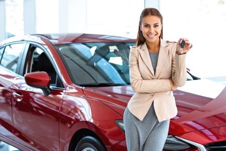 Foto van gelukkige jonge gemengd ras vrouw die sleutel toont aan haar nieuwe auto. Concept voor autoverhuur