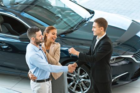 자동 쇼에서 성공적인 거래 후 구매자에 게 자동차 키를주는 젊은 남성 컨설턴트의 상위 뷰 사진. 렌터카 개념 스톡 콘텐츠