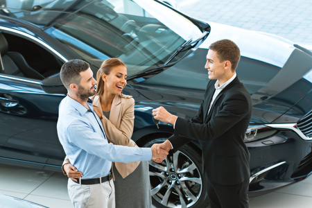 buying a car: Top view photo of young male consultant giving car key to buyers after successful deal in auto show. Concept for car rental Stock Photo