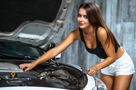 nude young: Фото молодой женщины ремонта автомобиля работника. Гламур сексуальная брюнетка носить джинсовые шорты. Девушка с гаечным ключом, глядя на камеру и работает под капотом автомобиля